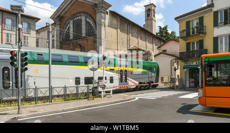 COMO, ITALY - JUNE 2019: Modern electric train passing over a road crossing as it departs from the town of Como on Lake Como. A bus is waiting at the - Stock Photo
