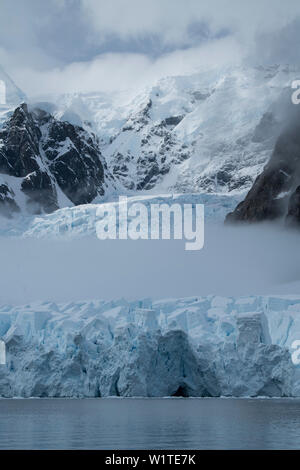 Fog cuts through the middle of a glacier crowned by mountains and clouds, Paradise Bay (Paradise Harbor), Danco Coast, Graham Land, Antarctica - Stock Photo