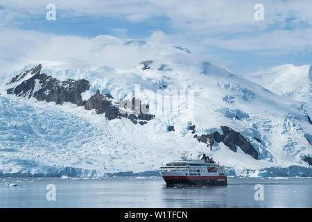 The Fram (Hurtigruten Group) makes way with a backdrop of steep snow and glacier covered mountains, Neko Harbour, Graham Land, Antarctica - Stock Photo