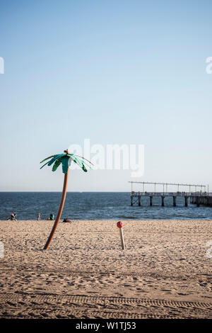 beach shower camouflaged as coconut palm tree on the beach of Coney Island, Steeplechase Pier in background, Brooklyn, NYC, New York City, United Stat - Stock Photo