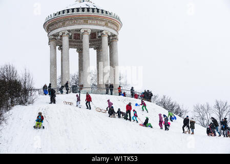 Sledging during Snow Fall at Monopteros, English Garden, Munich, Germany - Stock Photo