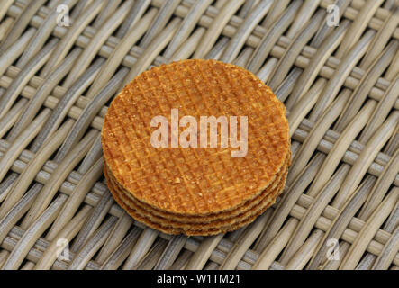 close up of stack of traditional dutch stroopwafels cookie, a caramel syrup waffle, on wooden background - Stock Photo