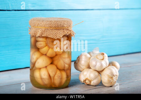 Pickled garlic in glass jar on wooden background - Stock Photo