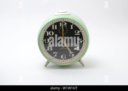 An old mechanical alarm clock, showing five o'clock