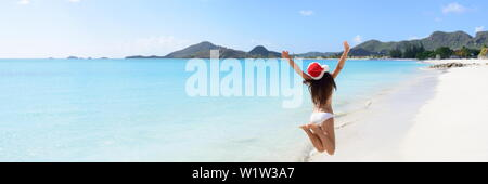 Woman with arms outstretched jumping at beach. Rear view of female is wearing Santa hat and bikini. Carefree tourist is enjoying Christmas vacation on sunny day. - Stock Photo