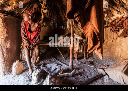 Young Himba man in his hut, Kunene, Namibia, Africa - Stock Photo