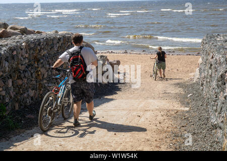 cyclists on a sunny summer day go down to the beach along with bicycles - Stock Photo