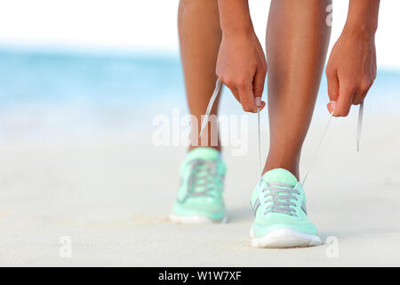 Runner woman tying laces of running shoes preparing for beach jogging. Closeup of hands lacing cross training sneakers trainers for cardio workout. Female athlete living a fit and active life. - Stock Photo