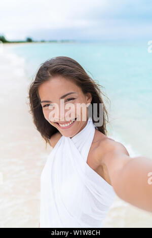 Selfie of beautiful Asian chinese caucasian mixed race woman on beach wearing white cover-up dress. Pretty young adult holding camera phone smiling during summer vacation caribbean travel. - Stock Photo