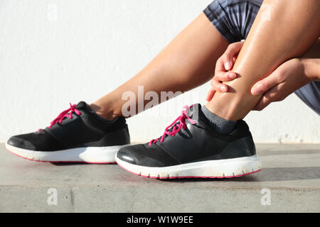 Ankle jogging injury female runner holding painful sprained ankle. Legs and running shoes closeup of woman hands gripping on leg in pain because of sore and injured joint and muscles in ankles. - Stock Photo