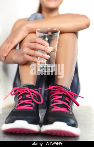 Fitness athlete woman drinking water holding glass - hand closeup hydration concept. Runner woman preventing dehydration for her health and body.