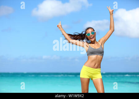 Happy cheerful fitness woman in sunglasses winning arms up doing v hand signs. Fit girl with slim body on sunny beach with raised arm showing peace sign in happiness of weight loss after workout. - Stock Photo