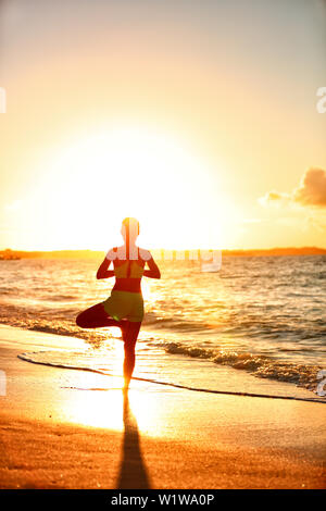 Meditation woman practicing Vriksasana tree yoga pose on beach at sunset. Serene young adult silhouette in morning sun flare balancing meditating doing a body workout. Wellness concept. - Stock Photo