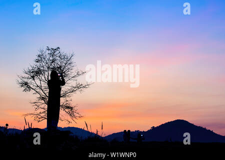 Tourists photograph the sunrise  behind the mountains. - Stock Photo