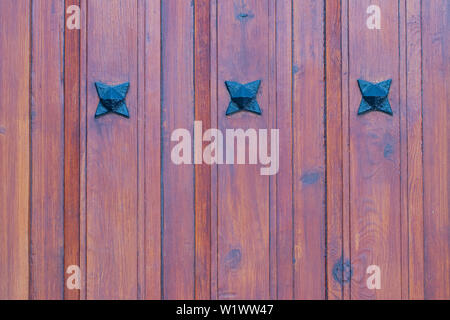 Wooden texture background. Closeup of a detail from a wooden red brown entrance door with three metal stars on the wooden planks. Macro. - Stock Photo