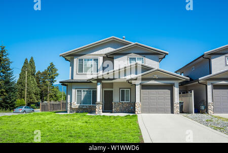 Half duplex residential building with concrete drive way and green lawn in front - Stock Photo