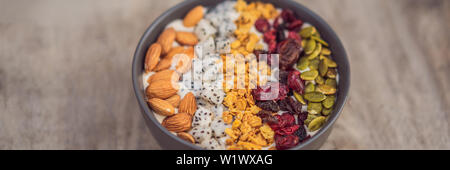 Mango smoothies bowl with almond, dragon fruit, dried cherries, pumpkin seeds and granola on wooden background BANNER, LONG FORMAT - Stock Photo
