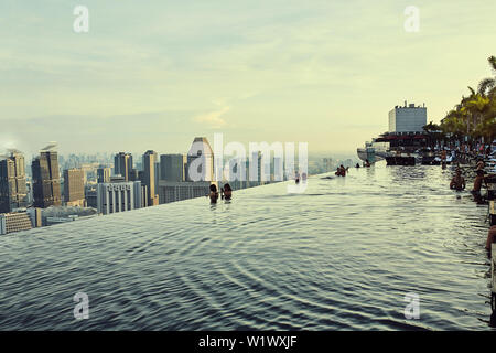 View over downtown Singapore from Marina Bay Sands Infinity pool at sunrise - Stock Photo