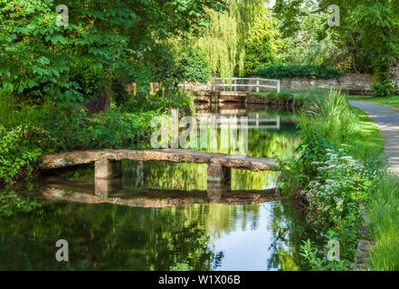 Old stone footbridge crossing the river Eye, in Lower Slaughter, Cotswolds, Gloucestershire, England, UK. - Stock Photo
