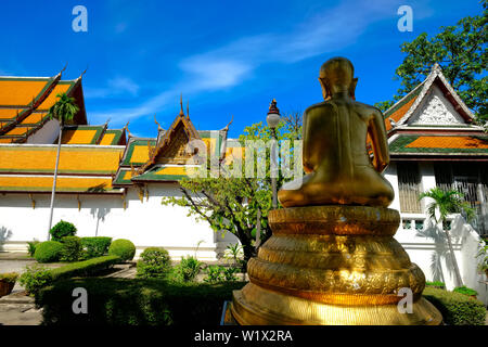A golden Buddha figure is seen from the back overlooking the buildings of Wat Suthat in Sao Ching-Cha (Giant Swing) area, Bangkok, Thailand - Stock Photo