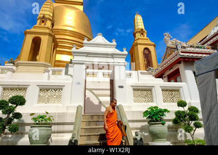 A Buddhist monk is seen descending from the platform around the large chedi (stupa) of Wat Boworniwet, in Banglamphoo area, Bangkok, Thailand - Stock Photo