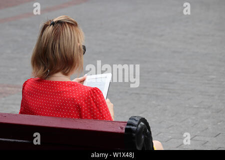 Young woman reads ebook on sitting on a bench on a city street. Concept of student, education, summer leisure - Stock Photo