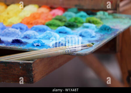 Brushes and palette with multi-colored paints. Concept of the artist studio, painting and creativity