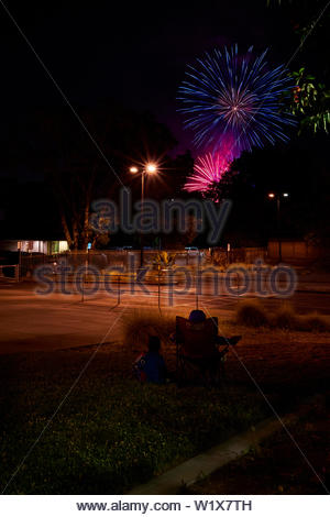Fireworks burst above trees and two kids look on during celebrations of Fourth of July, in Windsor, California. - Stock Photo