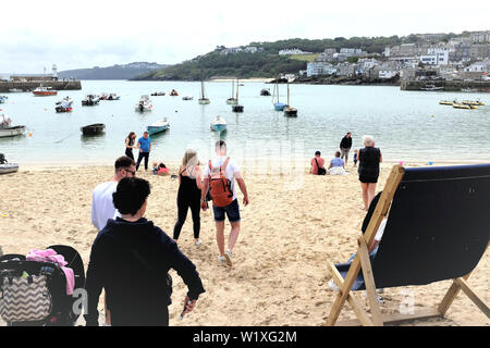 St. Ives, Cornwall, UK. June 24, 2019. Holidaymakers enjoying the sands overlooking the Harbor with high tide at St. Ives in Cornwall, UK. - Stock Photo
