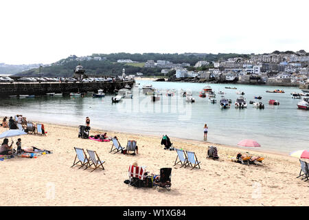 St. Ives, Cornwall, UK. June 25, 2019. Holidaymakers enjoying the sands of the harbor beach with a glorious view of the town and harbor at St. Ives in