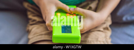 Young boy playing old school portable game console, electronic retro pocket toy with monochrome display BANNER, LONG FORMAT - Stock Photo