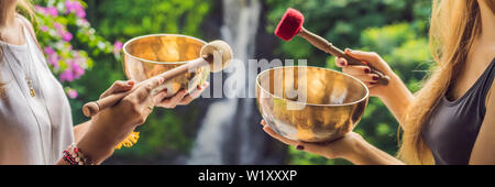 BANNER, LONG FORMAT Nepal Buddha copper singing bowl at spa salon. Young beautiful woman doing massage therapy singing bowls in the Spa against a - Stock Photo