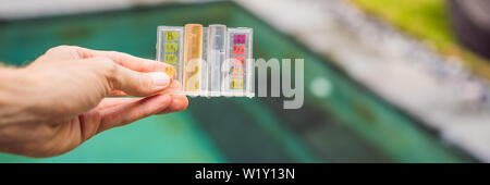 Measurement of chlorine and PH of a pool BANNER, LONG FORMAT - Stock Photo