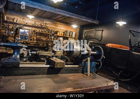 Workshop scene. Old tools hanging on wall in workshop, Tool shelf against a table and wall, vintage garage style - Stock Photo