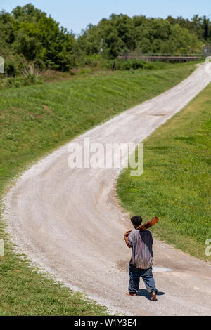 Buras, Louisiana - A barefoot African-American man carrying a guitar on his shoulder walks along a rural road in southern Louisiana. - Stock Photo
