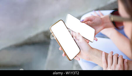 Two girls holding mobile smart phone next to each other sharing mockup white screen background clipping using smartphones blank working or looking on - Stock Photo