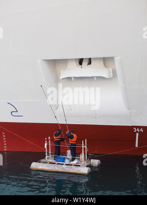 men painting anchor of cruise ship P and O Aurora - Stock Photo