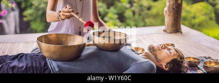 BANNER, LONG FORMAT Nepal Buddha copper singing bowl at spa salon. Young beautiful man doing massage therapy singing bowls in the Spa against a - Stock Photo