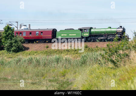 A steam train excursion is running from Liverpool Street in London to Dereham in Norfolk, passing through the Essex and Suffolk countryside. Seen climbing an embankment above the River Stour in Manningtree, Essex, the Steam Dreams Rail Co. special is being hauled by 61306 BR B1 Class 'Mayflower'. Resplendent in BR apple green the locomotive has recently been completely overhauled and returned to mainline specials in early 2019 - Stock Photo