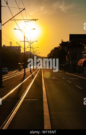 Urban city sunset vertical image of city street boulevard direct sunlight lens flare tram track tramway rails empty street trolleycar path - Stock Photo