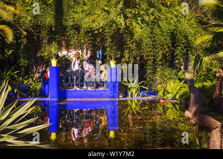 Visitors look at a pond in the Jardin Majorelle botanical garden in Marrakech - Stock Photo