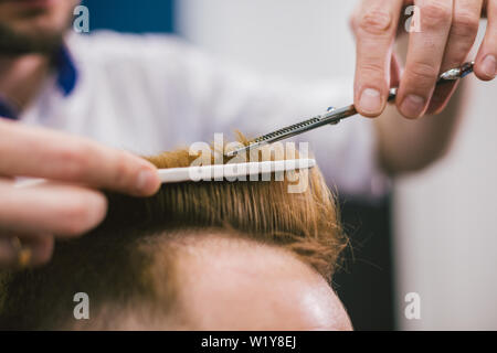 Barber Making Haircut Bearded Man In Barbershop. Professional stylist cutting client hair in salon. Barber using scissors and comb. Skillful hairdress - Stock Photo