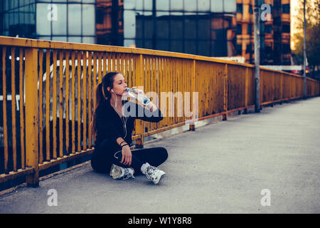 Female runner sitting on the bridge and drinking water from a bottle. Fitness woman taking a break after running workout. - Stock Photo