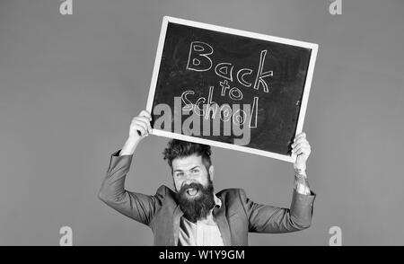 Stay positive. Keep working and be kind to people. Teacher bearded man holds blackboard with inscription back to school blue background. Teacher with tousled hair cheerful about school year beginning. - Stock Photo
