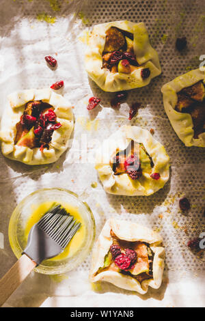 Plum tartelette are lined o cooking paper with egg yellow ready to be put in oven. - Stock Photo