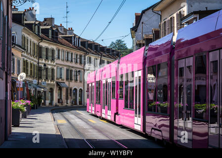 Tram passing through a typical street with  French-Italian architecture in the Carouge district, a Mediterranean style district modelled after Nice, G - Stock Photo