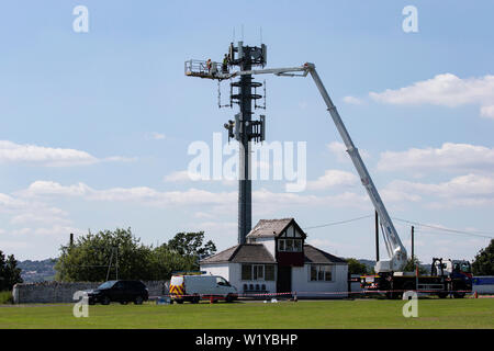 Large hydraulic crane lift being used by U.K. telecommunication engineers to upgrade the capability of a mobile phone mast - Stock Photo