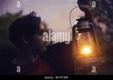 The guy stands at night in a dark scary forest with an old lighted kerosene lamp in his hand and looks into the darkness - Stock Photo