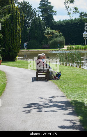 People relaxing and enjoying the bright summer sunshine overlooking a large lake - Stock Photo