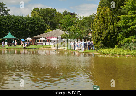 Large crowds of people at Burnby Hall Gardens, beginning a conducted tour of the water gardens which comprise the National collection of water lilies. - Stock Photo